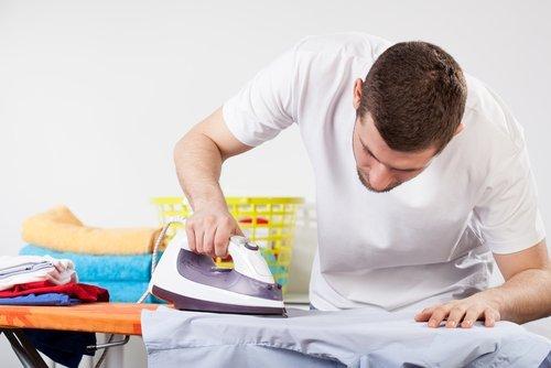 ragazzo concentrato per stirare camicia