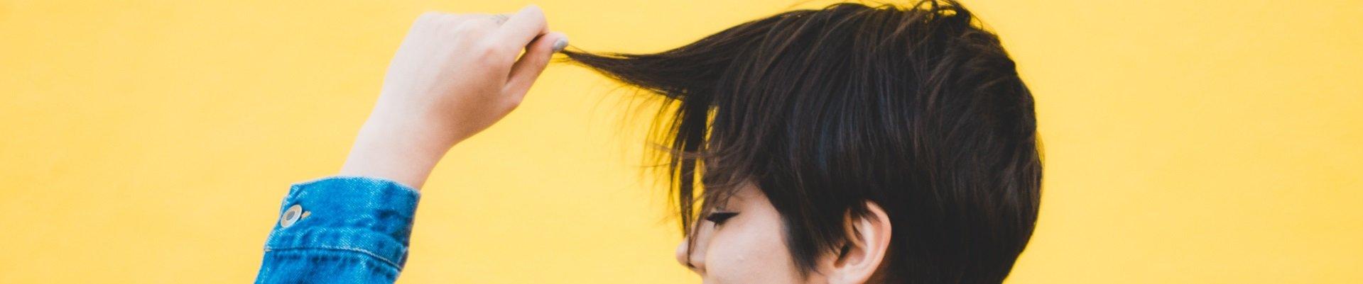 ragazza tira capelli corti
